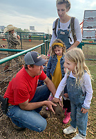Dwain Parsons (left) holds a shoat Wednesday, Oct. 6, 2021, as Sine Jones, 5, (right) of Bentonville and Evelyn Moyer, 5, of Rogers pet it as Elizabeth Jones (top) watches at Farmland Adventures in Springdale. The facility hosts a Mom's Day Out with reduced admission, which continues Oct. 11, 21 and 28. The attraction features hay rides, a corn maze, a petting zoo and is open through Nov. 6. Visit nwaonline.com/211007Daily/ for today's photo gallery.<br /> (NWA Democrat-Gazette/Andy Shupe)