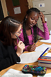Education classroom two female students working on math problem together