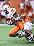 Oklahoma State Cowboys wide receiver Justin Blackmon (81) gets tackled by Texas Longhorns cornerback Curtis Brown (3)) during the game between the Oklahoma State Cowboys and the University of Texas in Austin Texas Longhorns at the Daryl K. Royal- Texas Memorial Stadium in Austin, Texas. The Oklahoma State Cowboys defeated the Texas Longhorns 33 to 16.