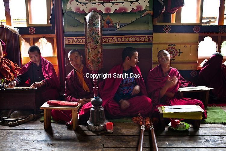 Buddhist monks share a light moment during their tea break after  reading their prayers inside the Ramtanka Temple in Paro, Bhutan. Photo: Sanjit Das/Panos