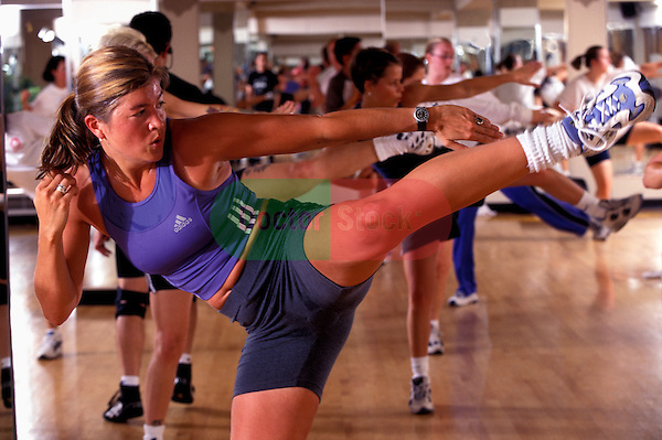 young woman instructor leading class with kickboxing move in health club studio