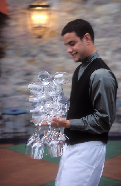 Napa Valley waiter carrys crystal wine glasses at Wine Spectator restaurant, of Culinary Institute of America in St. Helena, Ca