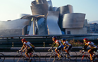 A group of cyclists race past the irregularly curved exterior of the striking Guggenheim Museum in Bilbao designed by Frank Gehry