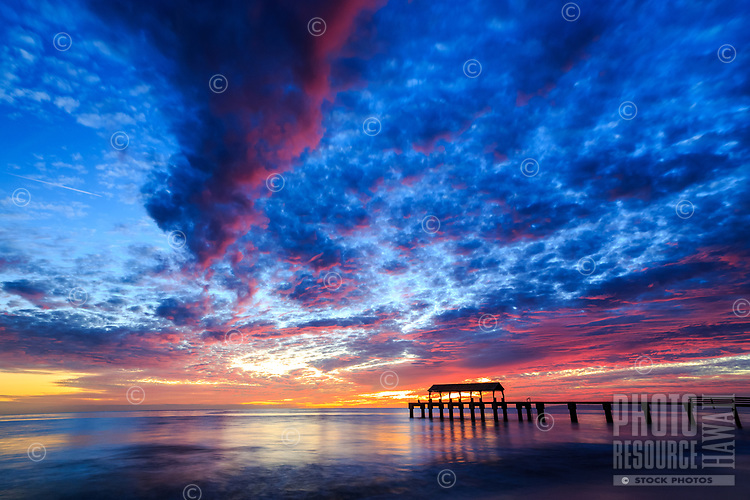 A brilliant blue and red sunset sky above Waimea Pier in Waimea, Kaua'i.