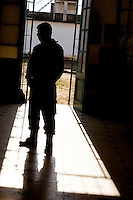 South America, Argentina, La Plata, Los Olmos. Freedom Behind Bars, Prison and Divinity - A guard in the corridor of Unit 25 of Los Olmos Prison. Los Olmos Prison is one of the principal security prisons in Argentina. It hosts Unit 25, known as Christ the Only Hope Prison Church, one of the largest prison churches worldwide. The transformation of criminals into the God fearing and leading them to the Lord has taken hold, not only in the lives of inmates, but also in inmate families and prison guards. Once the countries worst killers and thieves have since become spiritual leaders to other criminals, creating a revolutionary spiritual rehabilitation, July 2006 © Stephen Blake Farrington<br />