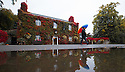 21/09/15<br /> <br /> After a heavy downpour, Boston Ivy Vine (or Japanese Creeper) growing on The Old Eyre Arms shows-off its stunning autumnal hues as publican, Nick Smith, is reflected in puddles outside his pub, in Hassop, near Bakewell in the Derbyshire Peak District. <br /> <br /> <br /> All Rights Reserved: F Stop Press Ltd. +44(0)1335 418365   www.fstoppress.com.