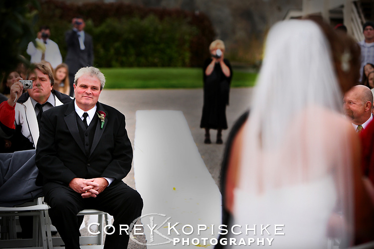 Father of the bride smiling at daughter during ceremony.