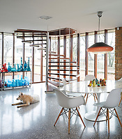 A dog lounges in dining area at the foot of a spiral staircase, next to a collection of colourful Murano glass.