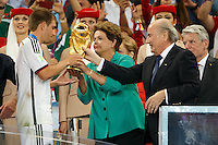 Philipp Lahm of Germany is given the World Cup trophy by FIFA President Sepp Blatter and Brazil President Dilma Rousseff