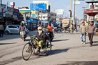 India, Dehradun.  Traffic at an Intersection, Man in a Three-wheeled Hand-powered Cycle.