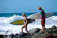 couple carrying surfboards on rocky grounds; surfing