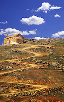 Spain. Castile la Mancha. Winding track leading to church, flock of sheep..