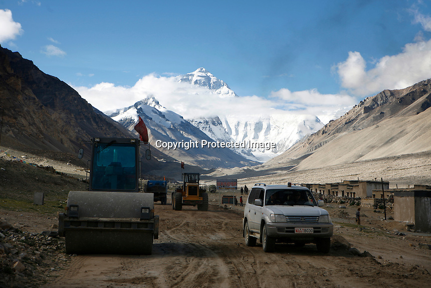 """China started building a controversial 67-mile """"paved highway fenced with undulating guardrails"""" to Mount Qomolangma, known in the west as Mount Everest, to help facilitate next year's Olympic Games torch relay./// A digger rolls past Rongbuk Monastery  on the road to Everest Base Camp.<br /> Tibet, China<br /> July, 2007"""