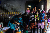 Women wait with their children, while a vaccinator gives the polio drops to an infant at a polio booth during Polio Day at a municipal office in Kolkata, West Bengal, India.<br /> On Polio Days, small booths are set up in different parts of the city, urging local residents to vaccinate their children below 5 years.
