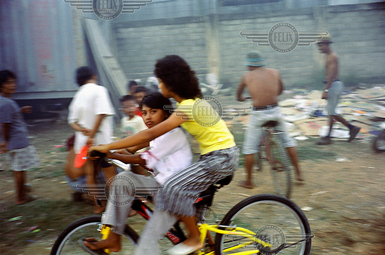 Children ride a bicycle whilst others play, outside their homes in a slum on Batam island.