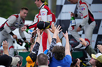 Fans jumping for WeatherTech hats during podium