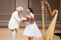 USA International Harp Competition Vice President Linda Wood Rollo, left, gives flowers to performer Valerie Sim during the Stars of Tomorrow Concert at the 11th USA International Harp Competition at Indiana University in Bloomington, Indiana on Thursday, July 11, 2019. (Photo by James Brosher)