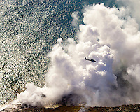 Aerial view of tour helicopter observing steam from lava meeting ocean.