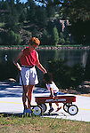 Mother helping daughter out of wagon on pedestrian path along Lake Estes, Estes Park, CO