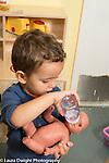 Education Preschool Child care two year old program boy playing feeding bottle to doll