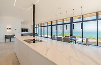 BNPS.co.uk (01202 558833)<br /> Pic: Strutt&Parker/BNPS<br /> <br /> Stunning views from the kitchen area...<br /> <br /> A former WW2 battery, with unrivalled views across the channel to France, has come on the market - but you'll need deep pockets to shell out on its stunning location.<br /> <br /> The cliff top gun emplacement was rapidly constructed in 1940, as Britsh troops were fleeing Dunkirk, and has now been transformed into a £6million 'James Bond style' property.<br /> <br /> The Gunnery, near Kingsdown in Kent offers 'incredible' views of the Channel, with the iconic White Cliffs of Dover visible to the west, and France to the south, while also coming with six acres of sandy beach.<br /> <br /> The unique 82ft long property is accessed by an underground tunnel that leads through the cliff to a glass lift which travels up to it. Another secret tunnel inside the four bedroom home, which is just a few feet from the cliff edge, provides passage to a home cinema.<br /> <br /> The 50ft long living room has floor to ceiling windows and the original gun loops can still be seen.