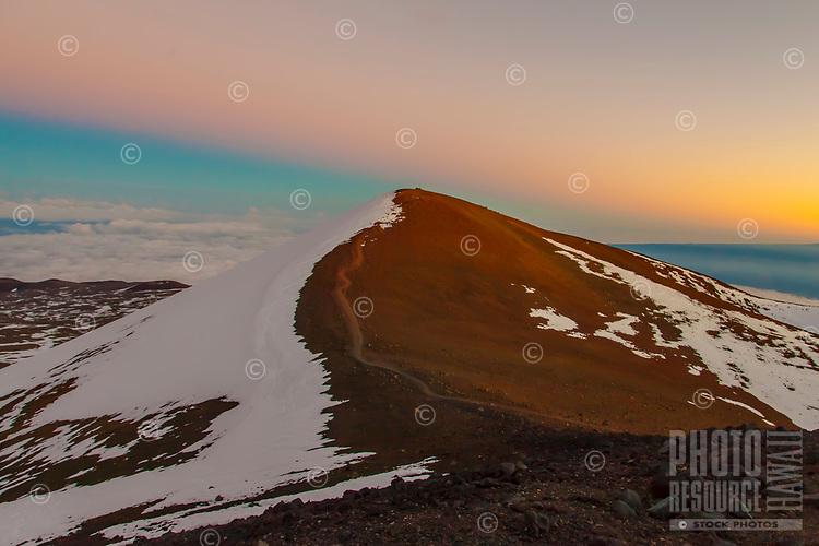 Mauna Kea Shadows: Mauna Kea mountain casts its own shadow during a colorful sunset over a sacred heiau on its summit, Hawai'i Island.
