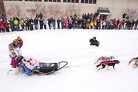 Saturday, March 3, 2012  DeeDee Jonrowe waves to the crowd along 4th avenue as she runs down the street after leaving the Ceremonial Start of Iditarod 2012 in Anchorage, Alaska.