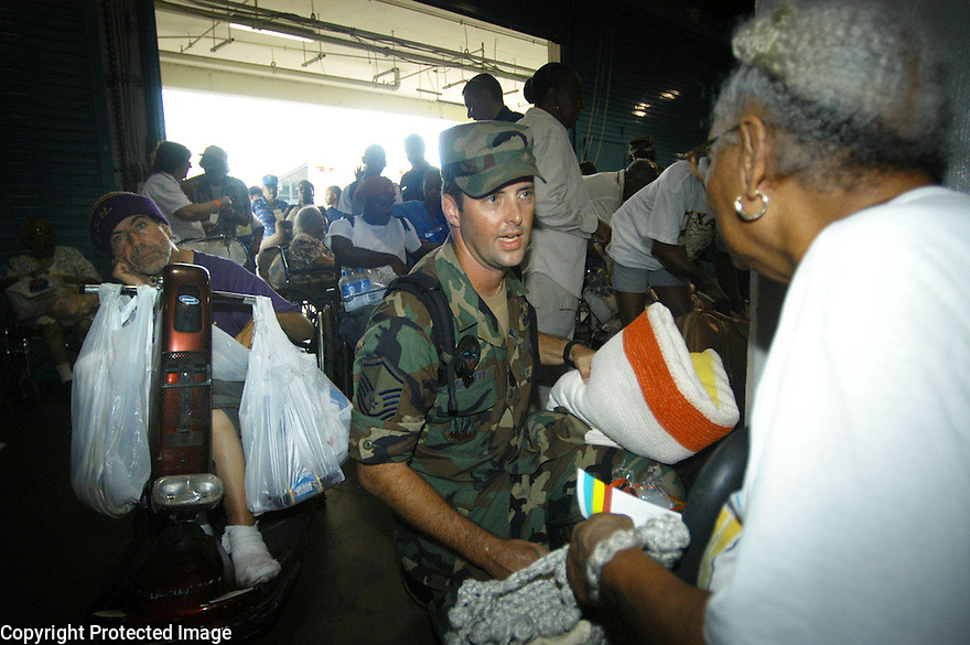 National Guardsman Kevin Bassett helps Enola Medial with her belongings at the Louisiana Superdome Sunday afternoon..(Cheryl Gerber Photo)