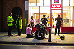 © Joel Goodman - 07973 332324 . 27/12/2017. Wigan, UK. Police officers ensure a man, dressed up as a fireman, is well, after a fall . Revellers in Wigan enjoy Boxing Day drinks and clubbing in Wigan Wallgate . In recent years a tradition has been established in which people go out wearing fancy-dress costumes on Boxing Day night . Photo credit : Joel Goodman