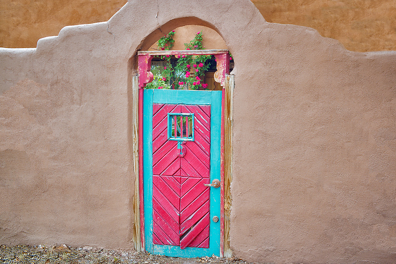 Red Histtoric door and adobe building near Santa Fe, New Mexico.
