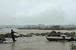 Maroon man trying to dislodge a dugout canoe from rapids on the Marowijne river, Suriname.