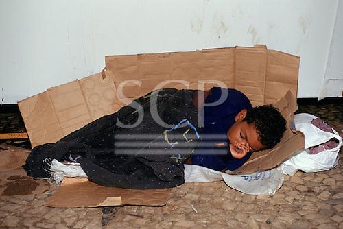 Salvador, Bahia State, Brazil; very young homeless street kid sleeping on a cardboard box in the street.