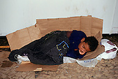 Salvador, Bahia State, Brazil; very young homeless street kid sleeping on a cardboard box in the street.