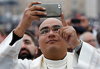 Un sacerdote scatta delle foto prima di una messa celebrata da Papa Francesco per l'apertura ufficiale del Giubileo della Misericordia, in Piazza San Pietro, Citta' del Vaticano, 8 dicembre 2015.<br /> A priest takes pictures prior to the start of a mass celebrated by Pope Francis to officially open the Jubilee of Mercy, in St. Peter's Square at the Vatican, December 8, 2015.<br /> UPDATE IMAGES PRESS/Riccardo De Luca<br /> <br /> STRICTLY ONLY FOR EDITORIAL USE