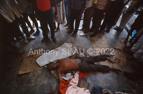 Port-au-Prince, Haiti.November 23, 1987..The man found dead at the Marché Salomon after a night of violence. The ton-ton-macoutes are suspected of creating the violence prior to elections being held on November 29th, the first attempt at a democratic election in Haiti. It was unsuccessful as 34 people were killed at a polling station and elections were moved up to February 1988...Leslie François Manigat won the election with many political parties boycotting. He had military backing but once in office he sought greater control over the military in an effort, to fight corruption. Manigat's government was overthrown by General Henri Namphy within months.