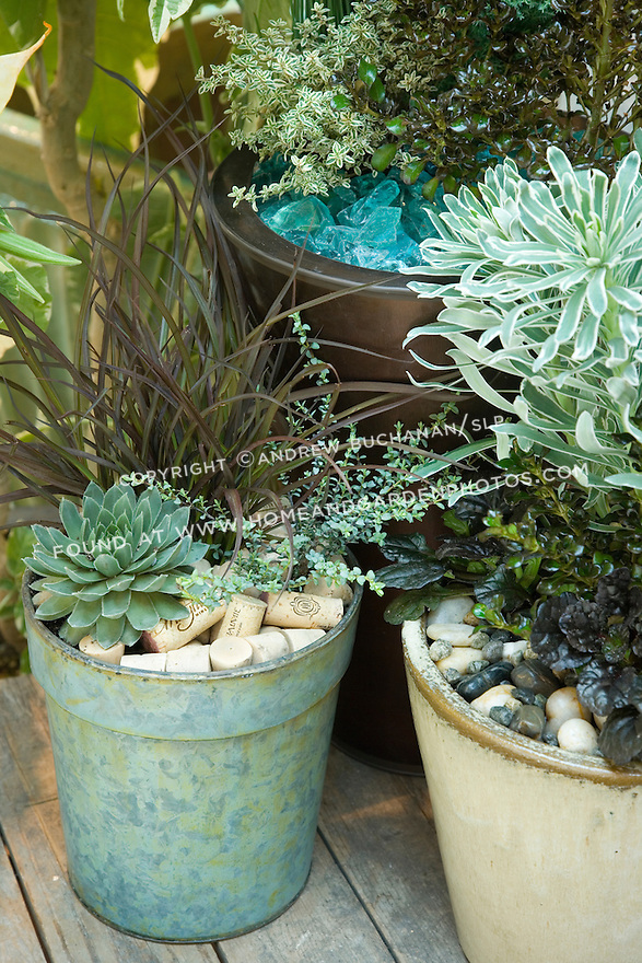 """In this blue-green motif, stones, corks, and aqua-colored tumbled glass share the mulching duties and mimic the colors of, among others, Hens-and-chicks 'Lavender and Old Lace' (left """"cork"""" pot, bottom left), silver thyme (left """"cork"""" pot, right side and rear copper pot, left side), Phormium 'Jack Spratt'  (left """"cork"""" pot, tall middle), Euphorbia 'Glacier Blue' (right """"stones"""" pot, tall middle), and Ajuga 'Black Scallop' (right """"stones"""" pot, low right)."""