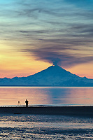 Photographer takes pictures of the plume of gas and vapor venting from the summit of Mt. Redbout volcano (10,191 ft), of the chigmit mountains, aleutian range. view across Cook Inlet approximately 50 miles, at sunset, southcentral, Alaska.