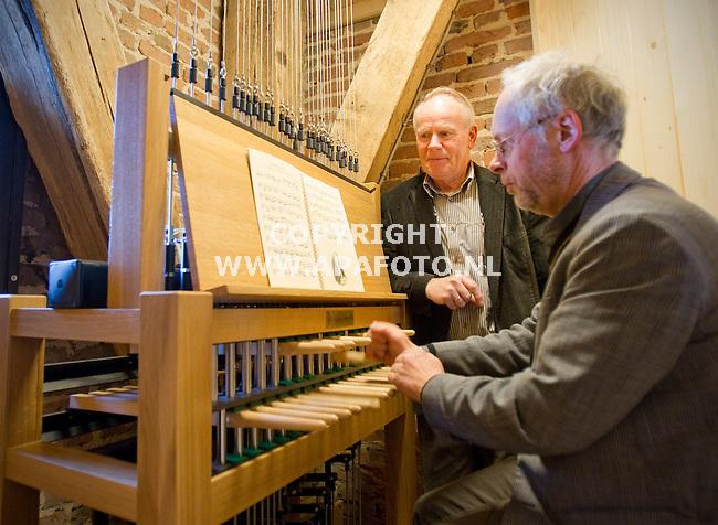 Bathmen, 230311<br /> Koster Ruiterkamp kijkt toe hoe beiaardier Jan Willem Achterkamp het carillon van de dorpskerk bespeelt. De raad van state heeft bepaalt dat er gespeeld mag worden. <br /> Foto: Sjef Prins - APA Foto