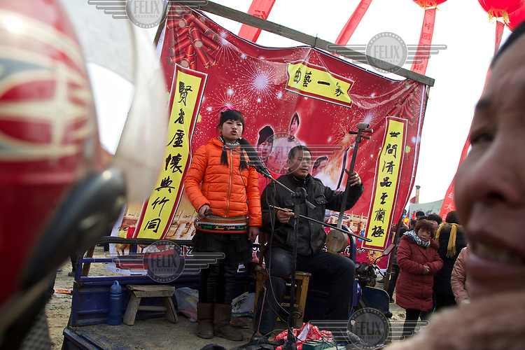 A traditional storyteller, accompanied by a musician, performs at the Ma Jie folk festival. <br /> <br /> For centuries farmers in Henan have gathered during Chinese New Year in the region's wheat fields to listen to bards singing and recounting old tales. <br /> <br /> Now storytellers come from all over China to attend the annual festival where large crowds gather to watch the best performers.