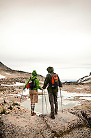 Hikers with trekking poles, pause above a frozen alpine tarn under a grey sky, The Enchantments, Alpine Lakes Wilderness, WA.