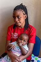 Africa, DRC, Democratic Republic of the Congo, Goma, Lake Kivu,  Global Fund for Women. Stop violence in schools campaign by the PAIF organization project. Immaculee Birkhaheka, founder of PAIF project. Kisonga Matondo (17 yrs). I am an orphan. My mother died when I was 3 months, my father when I was 8. At age 13 I was raped by my 52-year-old teacher while in secondary school. He put has hand over my mouth and used some kind of drug. When I came to I was covered in blood. I was afraid to tell anyone but I became pregnant--- my first baby is now 4 years old. The school did nothing. One day I accepted a ride from a man who gave me ride in his car because it was raining. He raped me. This baby is my second from a rape. When I became pregnant he took me in but beat me everyday, and I suffered so much. I soon discovered that I was his sixth wife and this was his 8th child so I left when this baby was one month old. I had no one to take care of me until I met with PAIF. PAIF will help me to take my husband to court and sue him but if they lose he will find me and kill me. There is no justice in this country.