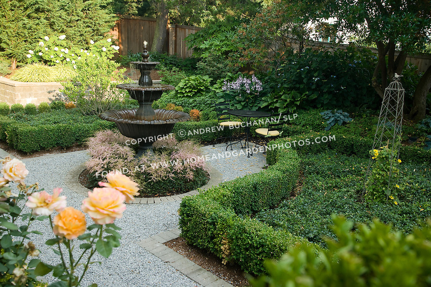 in a small formal garden behind this residence near Seattle, two black painted metal chairs sit beside the tall central water feature at the center of the gravel path, neatly clipped boxwood hedges, and rose bushes; Patrick residence