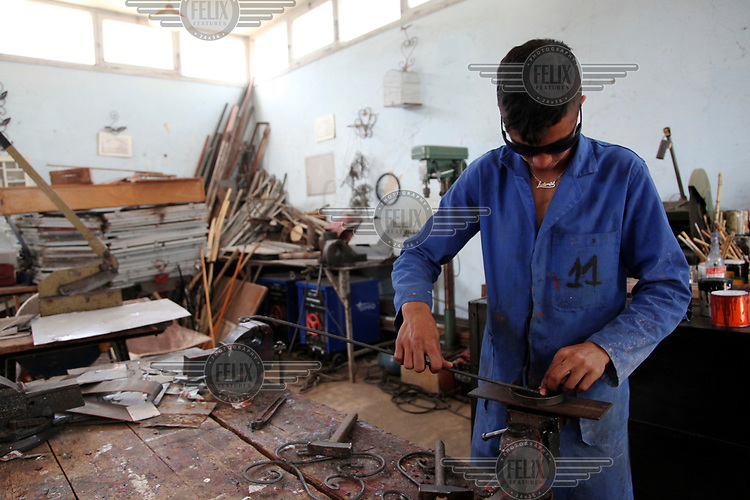 A youth uses tools in a workshop at the Center Abdelaziz Ben Driss which works with youths who have been in trouble with the authorities.