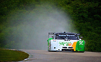 """The #61 BMW Riley of Mark Wilkins and Burt Frisselle kicks up a """"rooster tail"""" in the rain during practice, Road America, Elkhart Lake, Wisconsin.  (Photo by Brian Cleary/www.bcpix.com)"""