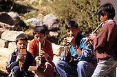 Ollantaytambo, Peru. Four boys playing pan pipes and kena flutes in the street.