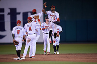 Lansing Lugnuts DJ Neal (7) high fives Otto Lopez (2) as Johnny Aiello (9), Rafael Lantigue (9), Griffin Conine (32), and Hunter Steinmetz (18) look on after a Midwest League game against the Burlington Bees on July 18, 2019 at Cooley Law School Stadium in Lansing, Michigan.  Lansing defeated Burlington 5-4.  (Mike Janes/Four Seam Images)