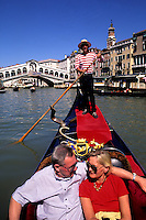 Tourists on romantic gondola ride near the famous Rialto Bridge with gondolier in picturesque Venice Ital