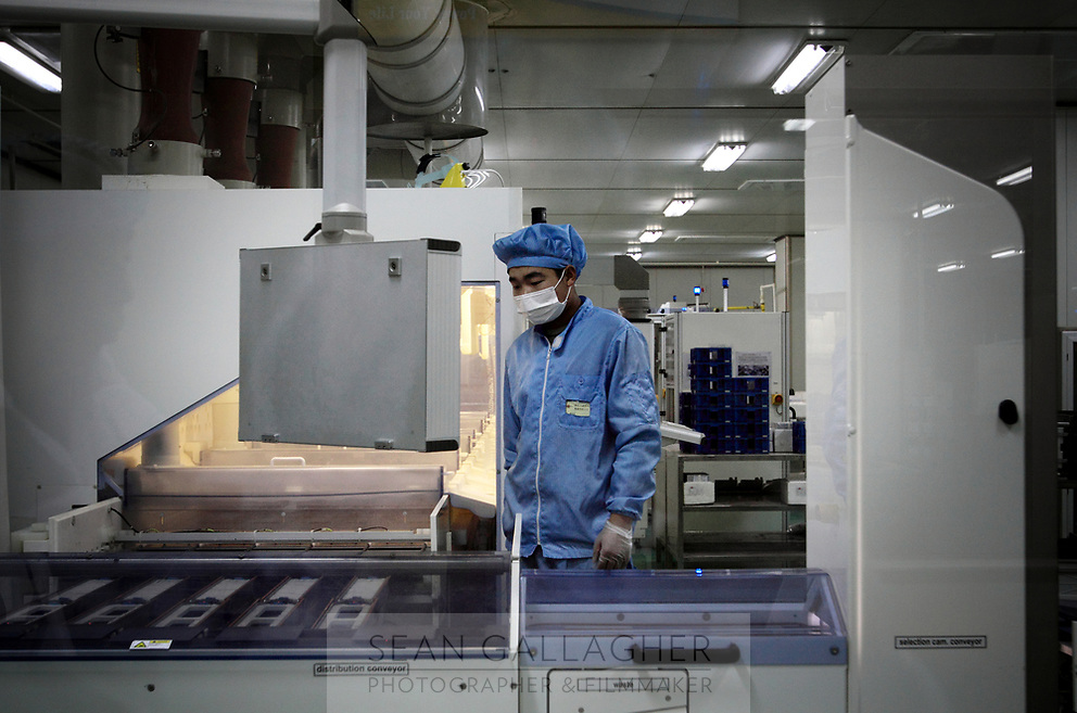 CHINA. Hebei.  A worker inside a factory producing solar panels in Baoding City near Beijing, the world's first 'carbon positive' town. The town's main industires focus on producing wind and solar technologies. 2009
