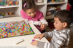 Education Preschool 3-4 year olds boy and girl playing board game taking turns