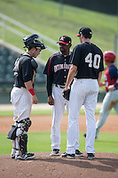 Kannapolis Intimidators pitching coach Jose Bautista (38) has a chat on the mound with starting pitcher Zach Thompson (40) and catcher Brett Austin (20) during the game against the Hagerstown Suns at CMC-Northeast Stadium on August 16, 2015 in Kannapolis, North Carolina.  The Suns defeated the Intimidators 7-2 in game one of a double-header.  (Brian Westerholt/Four Seam Images)